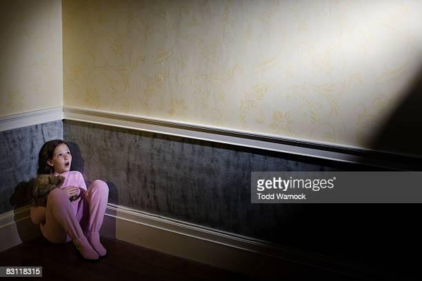 frightened girl in pajamas cowering in corner