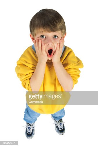 Frightened little boy with hands on face : Stock Photo