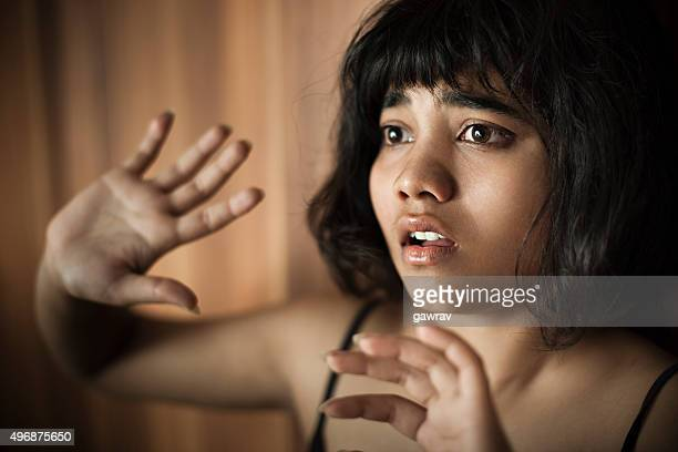 Frightened teenage girl looking away and hiding herself behind hands.