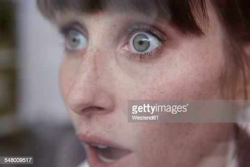 Frightened woman behind window