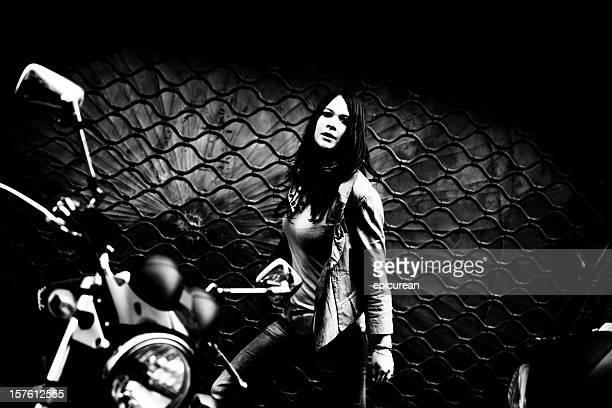 Frightened woman running down a dark street