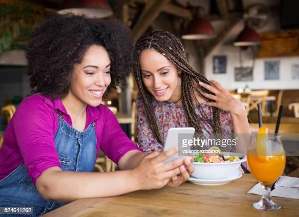 Amigos con teléfonos inteligentes en cafetería