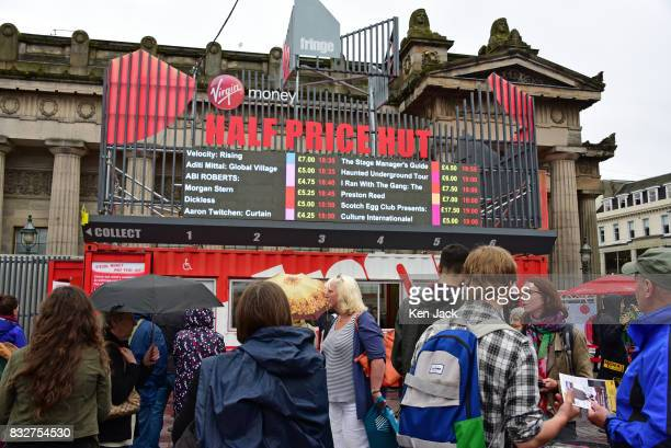 Fringegoers study shows on offer at reduced prices at the 'Half Price Hut' booking office during the Edinburgh Festival Fringe on August 16 2017 in...