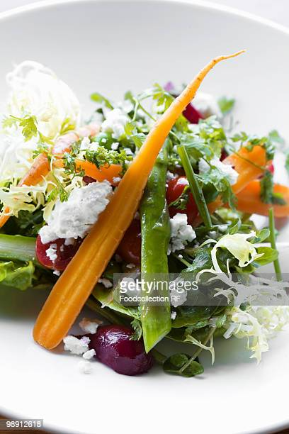 Frisee salad with carrots, asparagus, beets and feta, close-up