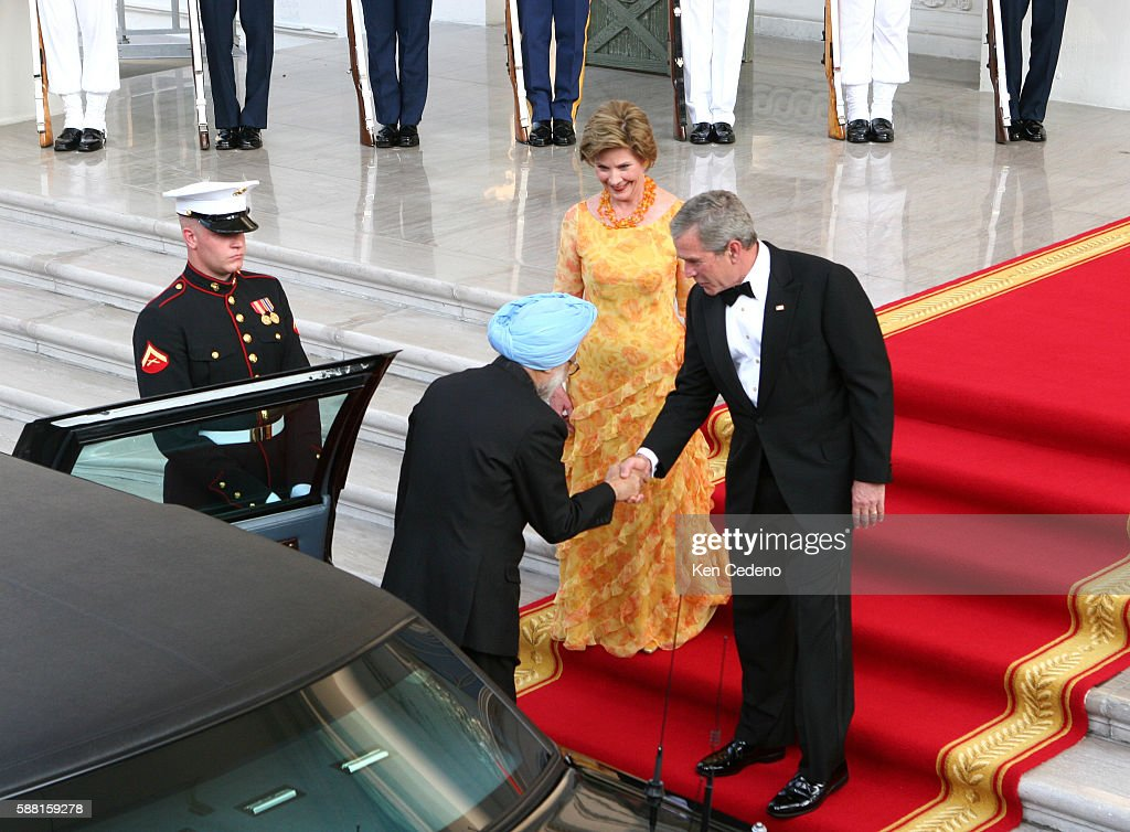Frist lady Laura Bush looks on as President George W Bush right greets Indian Prime Minister Manmohan Singh July 18 2005 in the North Portico of the...