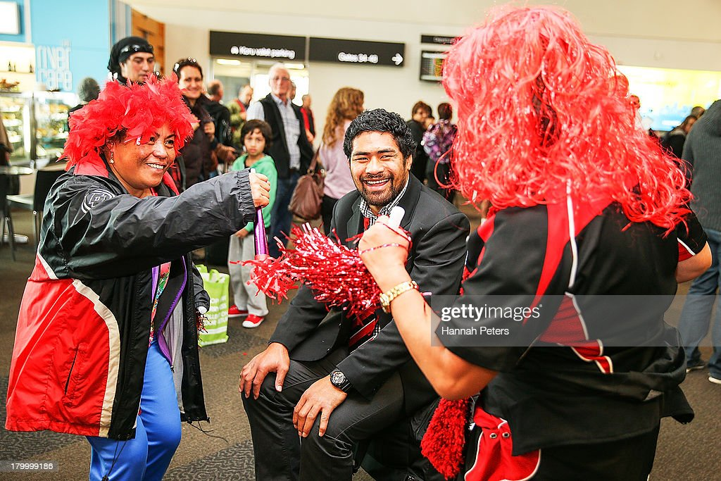 Fritz Lee of Counties Manukau waits for his ride as supporters dance around him after arriving with the Ranfurly Shield at Auckland Airport on...