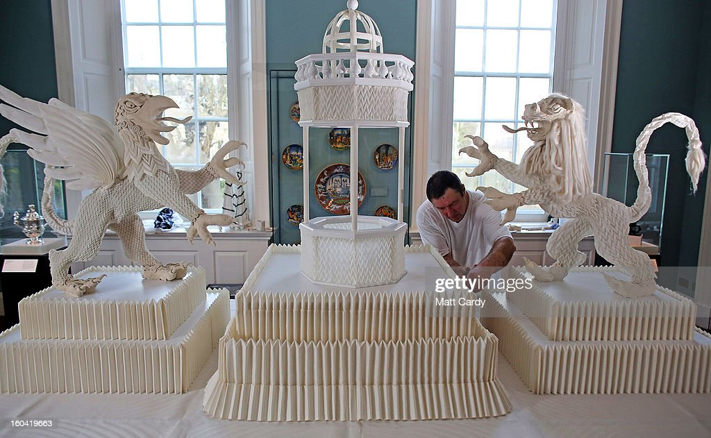 Frohmut Zscheckel helps put the finishing touches to artist Joan Sallas' 1.5-metre-high folded linen table fountain he is displaying as part of a new exhibition 'Folded Beauty: Masterpieces in Linen', which is opening at the Holbourne Museum on January 31, 2013 in Bath, England. The exhibition of the lost art of linen folding, examples of which would once have graced the dining tables of Kings and Emperors in seventeenth century Europe, will include animals, flowers and even miniature buildings and fountains all made from intricately starched and folded linen. This is the first UK exhibition by the world's leading authority on historic linen folding who has previously exhibited his work across Europe and the USA.