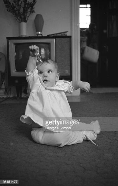 From a series entitled 'Grapsing' a child seated on the floor plays with a short chain of keyrings 1960s