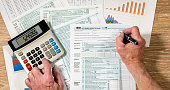 Senior man completing USA tax form 1040 for 2017 with charts and calculations on wooden desk