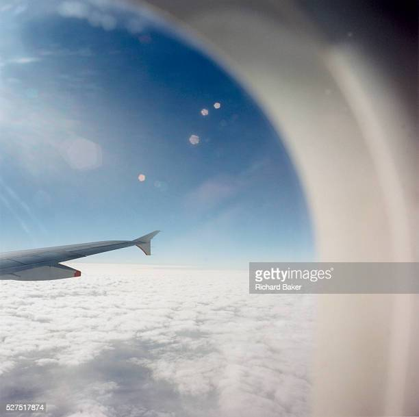 From an airliner passenger seat bright sunshine causes lens flare during a flight across the English Channel between Paris and London We see out at a...