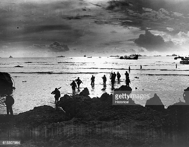 From Coast Guardmanned landing craft American invaders wade through a golden shallow surf to hit the beach of Tinian Island Units of a mighty task...