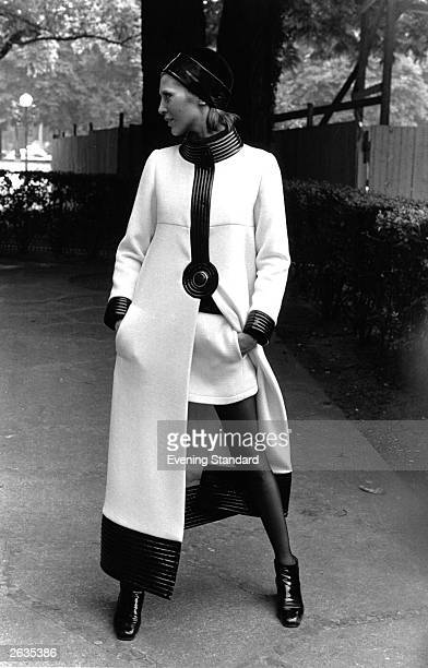 From French Fashion designer Pierre Cardin a long white coat trimmed with black and worn over a short white skirt and black tights and shoes This is...