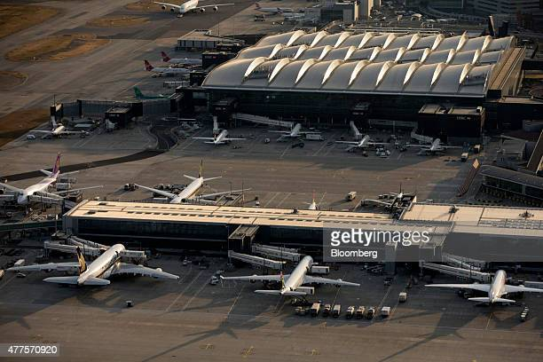 From front left to right aircrafts from Singapore Airlines South African Airways and Ethiopian Airlines sit at a passenger terminal building at...