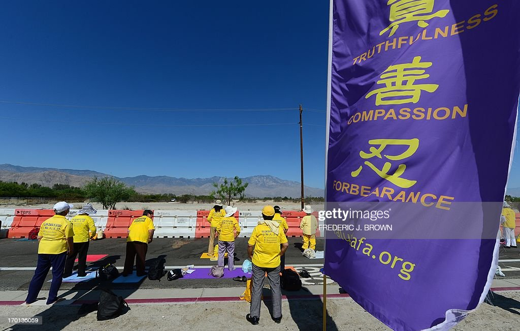 From inside a cordoned off protest zone, Falungong practioners do their exercise facing the direction of where President Barack Obama is due to meet his Chinese counterpart in the California desert community of Rancho Mirage, a little over 100 hundred miles east of Los Angeles, on June 7, 2013, where they were joined by supporters of the Tibetan cause in protesting the brutal repression of China's ruling Communist Party. Xi, the Chinese leader arrived in southern California the previous evening and stayed in a nearby hotel, according to the local Desert Sun newspaper, ahead of what was planned as an unusually relaxed US-China summit. AFP PHOTO/Federic J. BROWN