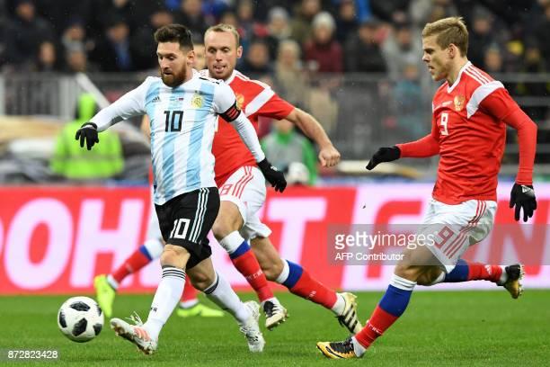 Argentina's Lionel Messi Russia's midfielder Denis Glushakov and Russia's forward Alexander Kokorin vie for the ball during an international friendly...