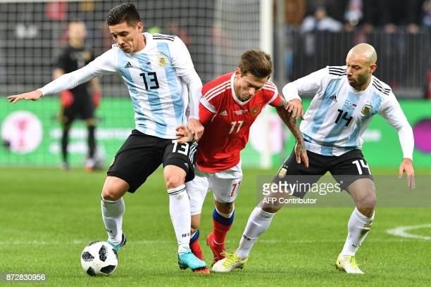 Argentina's Matias Kranevitter Russia's forward Fedor Smolov and Argentina's Javier Mascherano vie for the ball during an international friendly...