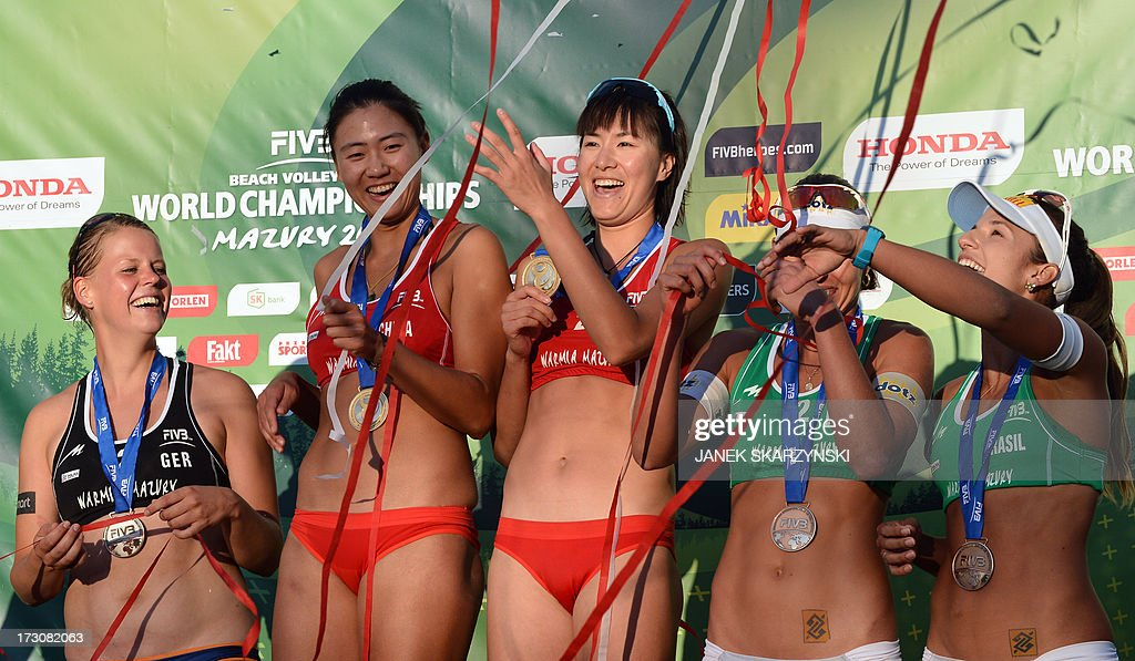 From L, Germany's Britta Buethe, second place, the winners China's Chen Xue and Xi Zhang and third place Brazilians Barbara Seixas De Freitas and Liliane Maestrini celebrate on the podium after the the Beach Volleyball World Championships on July 6, 2013 in Stare Jablonki.