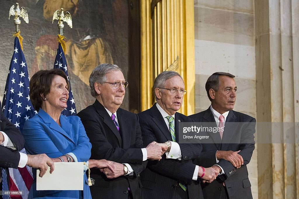 From L, House Minority Leader Nancy Pelosi (D-CA), Senate Minority Leader Mitch McConnell (R-KY), Senate Majority Leader Harry Reid (D-NV), and Speaker of the House John Boehner (R-OH) lock arms as they sing 'We Shall Overcome' during a ceremony to posthumously award the Congressional Gold Medal Dr. Martin Luther King, Jr. and Coretta Scott King, on Capitol Hill, June 24, 2014 in Washington, DC. The Congressional Gold Medal is Congress's highest civilian honor.