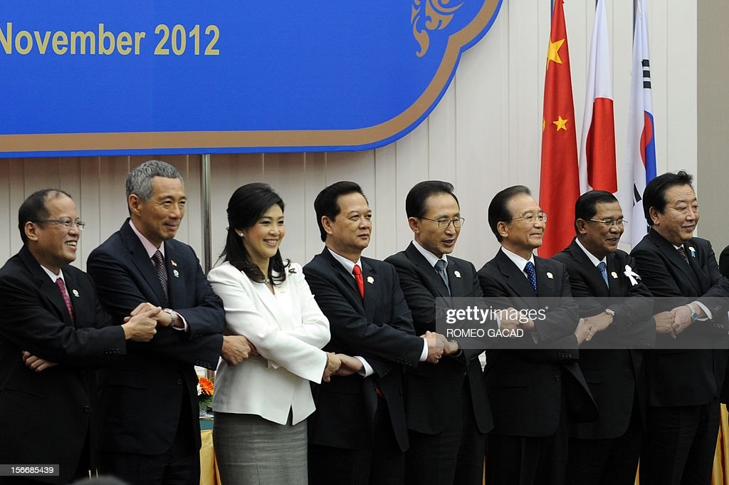 Philippines President Benigno Aquino, Singapore Prime Minister Lee Hsien Loong, Thai Prime Minister Yingluck Shinawatra, Vietnamese Prime Minister Nguyen Tan Dung, South Korean President Lee Myung Bak, Chinese Premier Wen Jiabao, Cambodian Prime Minister Hun Sen and Japan Prime Minister Yoshihiko Noda join hands together for a photo session during the Association of Southeast Asian Nations (ASEAN) Plus Three Commemorative Summit in Phnom Penh on November 19, 2012 following the 21st ASEAN Leaders Summit.