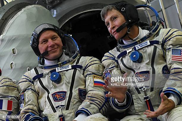 Russia's cosmonaut Oleg Novitsky and US astronaut Peggy Whitson pose for pictures in front of a Soyuz space vehicle simulator during an examination...
