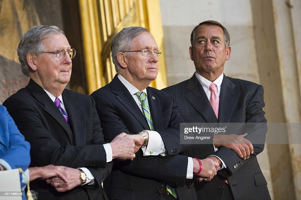 From L, Senate Minority Leader <a gi-track='captionPersonalityLinkClicked' href=/galleries/search?phrase=Mitch+McConnell&family=editorial&specificpeople=217985 ng-click='$event.stopPropagation()'>Mitch McConnell</a> (R-KY), Senate Majority Leader <a gi-track='captionPersonalityLinkClicked' href=/galleries/search?phrase=Harry+Reid+-+Politician&family=editorial&specificpeople=203136 ng-click='$event.stopPropagation()'>Harry Reid</a> (D-NV), and Speaker of the House <a gi-track='captionPersonalityLinkClicked' href=/galleries/search?phrase=John+Boehner&family=editorial&specificpeople=274752 ng-click='$event.stopPropagation()'>John Boehner</a> (R-OH) lock arms as they sing 'We Shall Overcome' during a ceremony to posthumously award the Congressional Gold Medal Dr. Martin Luther King, Jr. and Coretta Scott King, on Capitol Hill, June 24, 2014 in Washington, DC. The Congressional Gold Medal is Congress's highest civilian honor.