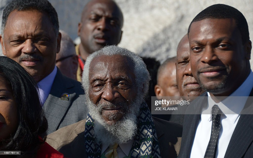 From L to R, Reverend Jesse Jackson, actor Dick Gregory and actor Chris Tucker attend a Martin Luther King Day ceremony under the statue of civil rights leader Martin Luther King, Jr. at the MLK Memorial on January 20, 2013 in Washington. King is best known for his role in the advancement of civil rights using nonviolent civil disobedience. AFP PHOTO / JOE KLAMAR