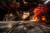 From ladle pours red-hot steel. Foundry. Martin furnace.