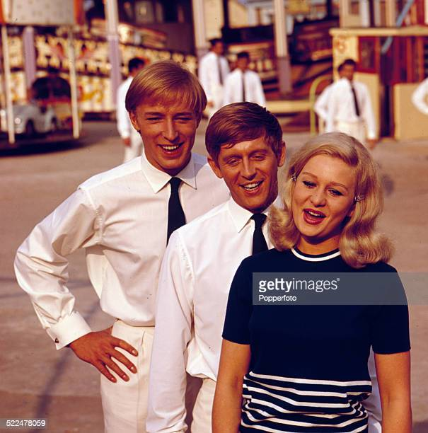 From left actors and singers Mike Sarne John Leyton and actress Grazina Frame posed together on the set of the film 'Seaside Swingers' in 1964