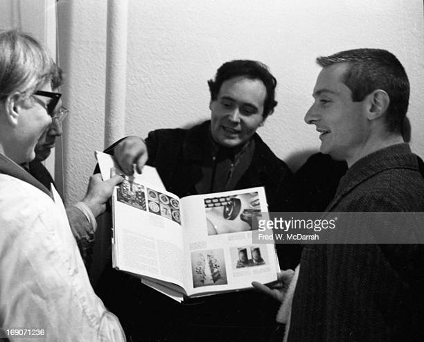 From left American Pop artists Andy Warhol Robert Indiana and Roy Lichtenstein flip through an art book as they attend an exhibit at the Iolas...