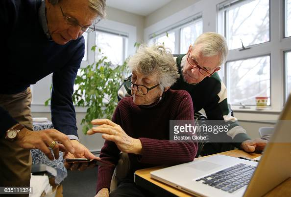 From left Bob Lotz Camilla Blackman and Bill Knuf set up Blackman's phone to receive calls during a training session for Groton Neighbors staff in...