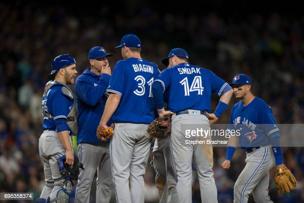 From left catcher Russell Martin of the Toronto Blue Jays pitching coach Pete Walker starting pitcher Joe Biagini of the Toronto Blue Jays first...