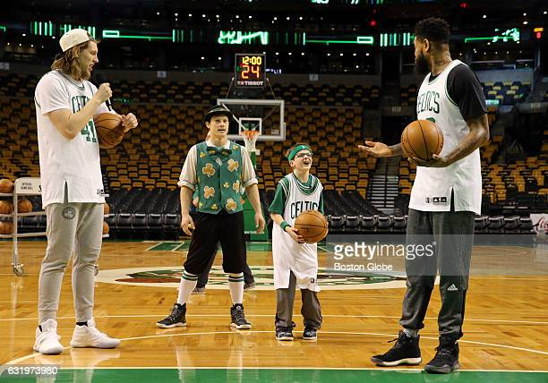 From left Celtics center Kelly Olynyk mascot Lucky Stephen Register and power forward Amir Johnson share a laugh while playing basketball at TD...