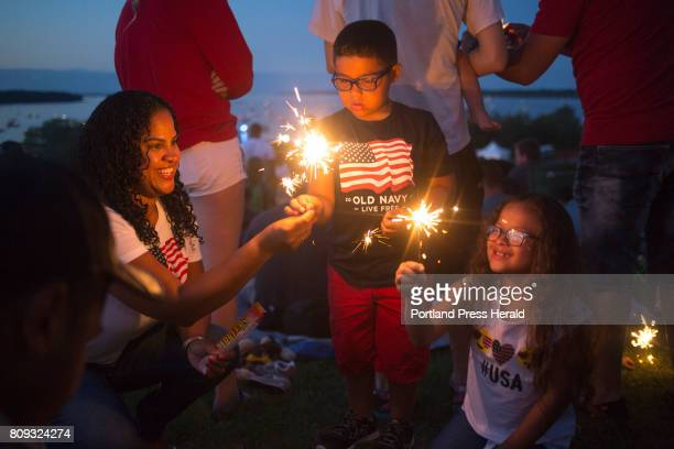 From left Debra Orellana Erik Orellana and Vanessa Orellana of Portland light sparklers as they wait to watch the fireworks at the Fourth of July...