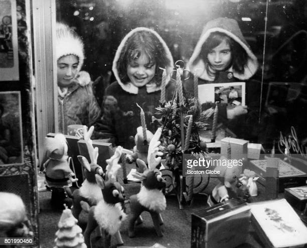 From left Elaine Mario Liza Bowe Jacqueline Bowe all of Allston look over the Christmas scene in a store window in Boston Dec 20 1968
