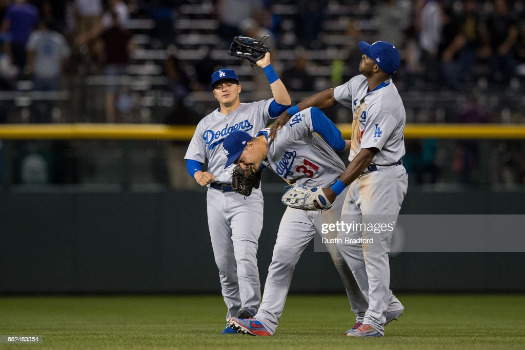 From left, Enrique Hernandez #14, Joc Pederson #31, and Yasiel Puig #66 of the Los Angeles Dodgers celebrate after a 6-2 win over the Colorado Rockies at Coors Field on May 12, 2017 in Denver, Colorado.