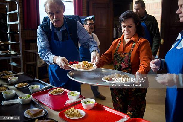 From left Erik Greven and Loretta Rowe both members of the Portland Rotary Club bring out the plates from the kitchen at the St Vincent DePaul's...