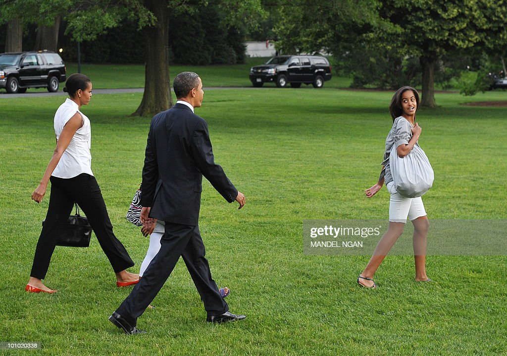 First Lady Michelle Obama, daughter Sasha (obscured), US President Barack Obama, and their daughter Malia make their way to board Marine One May 27, 2010 on the South Lawn of the White House in Washington, DC. Obama and his family were heading to Chicago to spend the Memorial Day weekend. AFP PHOTO/Mandel NGAN