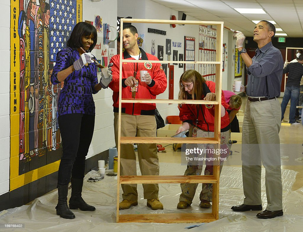 JANUARY 19 -- From left First Lady Michelle Obama, Jeff Franco, Executive Director of City Year, Sheri Fisher, a City Year employee and President Barack Obama stain bookshelves during a National Day of Service at Burrville Elementary School in Northeast Washington, participate in a Day of Service in Washington, D.C., on Saturday, January 19, 2013. About 500 volunteers participated in a school makeover.