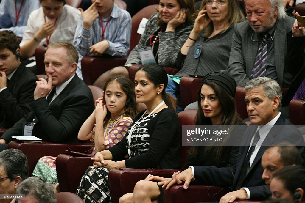 French luxury and retail group PPR Chairman and CEO Francois-Henri Pinault (L) his daughter Valentina, his wife actress Salma Hayek Pinault, Amal Clooney and her husband actor George Clooney attend an audience of Pope Francis to the participants of the Sixth World Congress of Pontifical Foundation Scholas, on May 29, 2016 in Vatican. Scholas is an international organization of pontifical right approved and created by Pope Francis in Vatican City August 13, 2013. It combines technology with art and sport to promote social integration and culture of encounter for peace. / AFP / VINCENZO