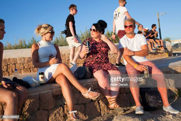 From left friends Charlene 27 Lucie Jade and Dan wait for the sun to set on San Antonio beach