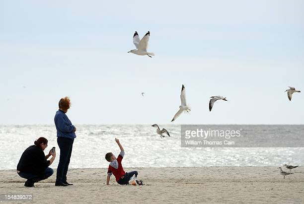 From left Gretchen Rundecker Pat Rundecker and Caiden Rundecker of Haskell New Jersey feed seagulls on the beach as the town prepares for Hurricane...