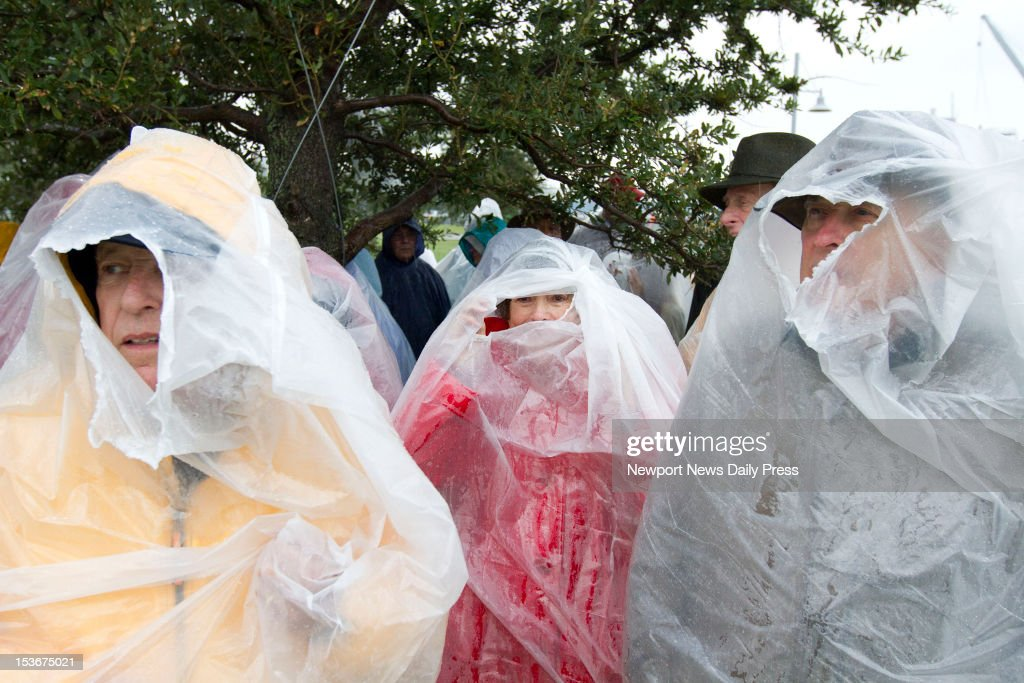From left, Jack Potters of Newport News, Va., Mary Lou Mason of Yorktown, Va., and Doug Shires of Williamsburg, Va., try to keep dry before a campaign rally Republican presidential nominee Mitt Romney at Victory Landing Park in Newport News, Virginia, on Monday, October 8, 2012.