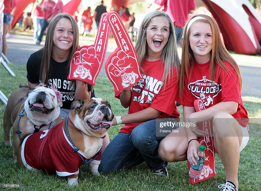 From left, Joelle Kircher, Tessa Hammerschmidt, and Kelsey Cummings, all 13, of Fresno, California, have their picture taken with English Bulldogs Hazel, left, and Sparky, prior to Fresno State playing host to Weber State at Bulldog Stadium in Fresno, California, on Saturday, September 1, 2012.
