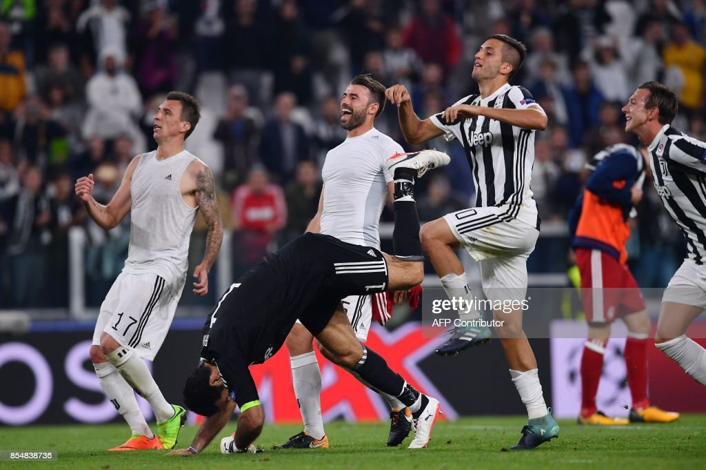 Juventus' forward from Croatia Mario Mandzukic, Juventus' goalkeeper from Italy Gianluigi Buffon, Juventus' defender from Italy Andrea Barzagli and Juventus' midfielder from Uruguay Rodrigo Bentancur celebrate at the end of the UEFA Champion's League Group D football match Juventus vs Olympiacos on September 27, 2017 at the Juventus stadium in Turin. Juventus won 2-0. / AFP PHOTO / Marco BERTORELLO
