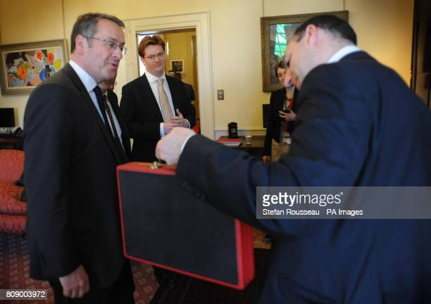 From left Mark Hoban and Danny Alexander look on as Dan Rosen Field holds Chancellor of the Exchequer George Osborne's new budget box before leaving...