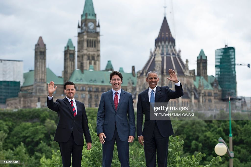 From left Mexican President Enrique Pena Nieto, Canadian Prime Minister Justin Trudeau and US President Barack Obama pose for a group photo with Canad's Parliament Hill in the background during the North American Leaders Summit on June 29, 2016 in Ottawa, Ontario. / AFP / Brendan Smialowski