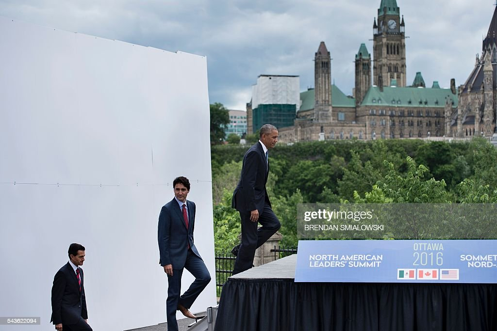 From left Mexican President Enrique Pena Nieto, Canadian Prime Minister Justin Trudeau and US President Barack Obama arrive for a group photo with Canad's Parliament Hill in the background during the North American Leaders Summit on June 29, 2016 in Ottawa, Ontario. / AFP / Brendan Smialowski