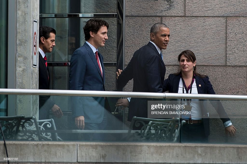 From left Mexican President Enrique Pena Nieto, Canadian Prime Minister Justin Trudeau and US President Barack Obama walk to a group photo with Canad's Parliament Hill in the background during the North American Leaders Summit on June 29, 2016 in Ottawa, Ontario. / AFP / Brendan Smialowski