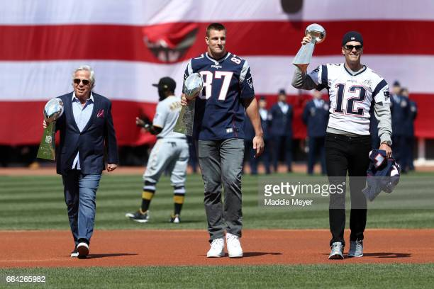 From left New England Patriots owner Robert Kraft Rob Gronkowski and Tom Brady walk onto the field carrying Vince Lombardi trophies before the...