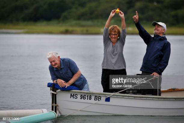 From left officials Mike Walker Karen Quigley and Mark Strauss display the winning duck during the Allens Pond Duck Derby on Barney's Joy Farm in...